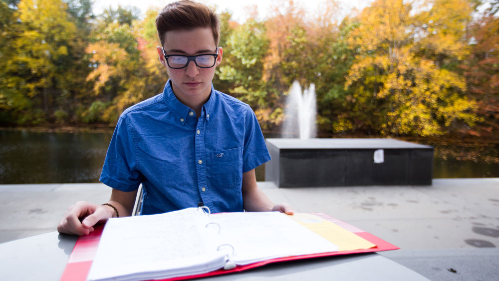 A Rowan University student studying outside Engineering Hall by the Lake