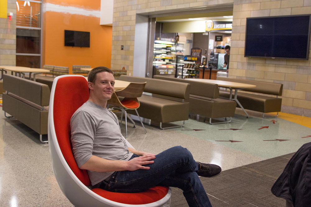 male student wearing gray shirt sits in an orange chair in the building lobby
