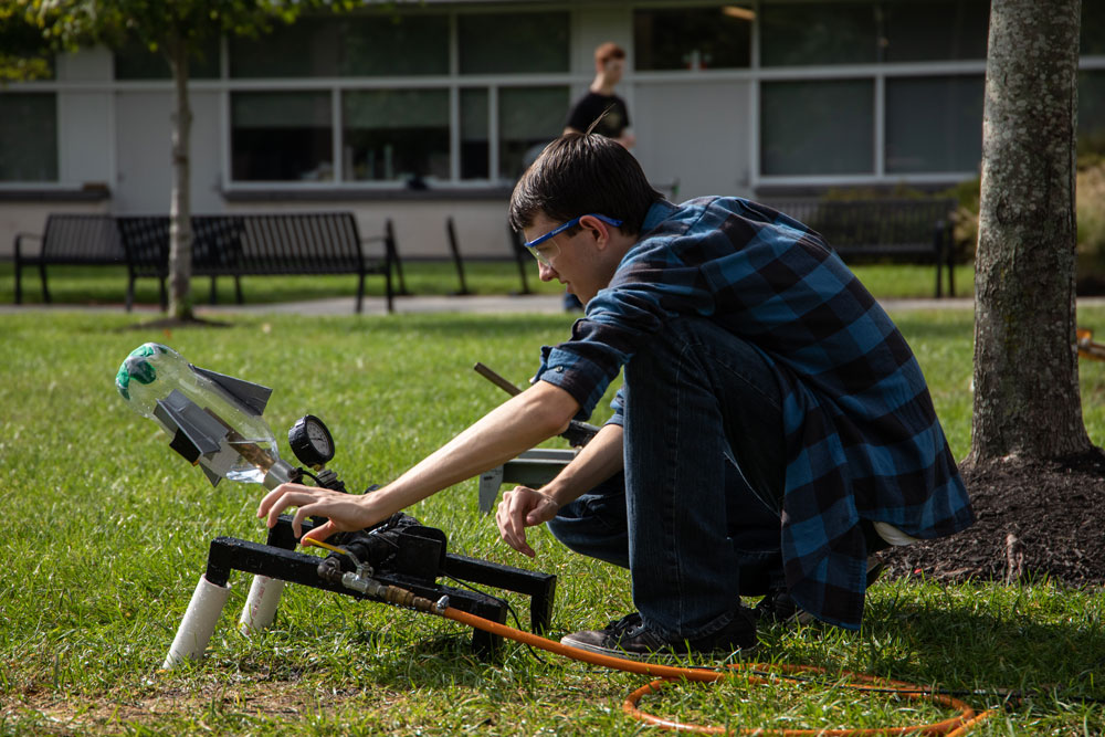 A male student adjusting a handmade water bottle launcher