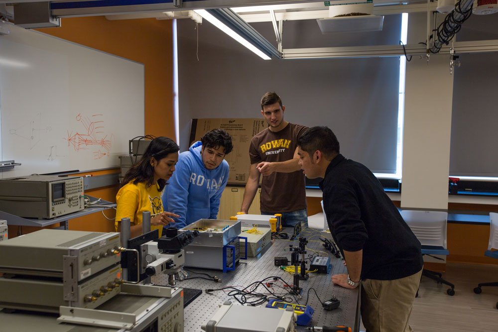 Four engineering students working at a lab table covered in wires